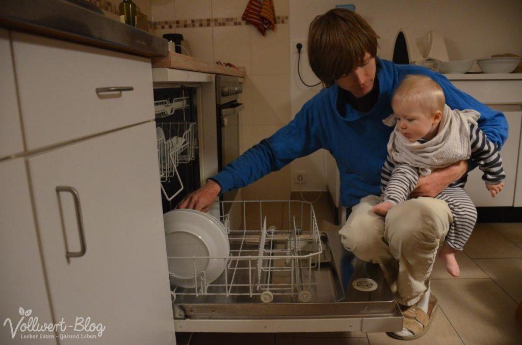Geschirrspüler ausräumen mit Baby auf dem Arm